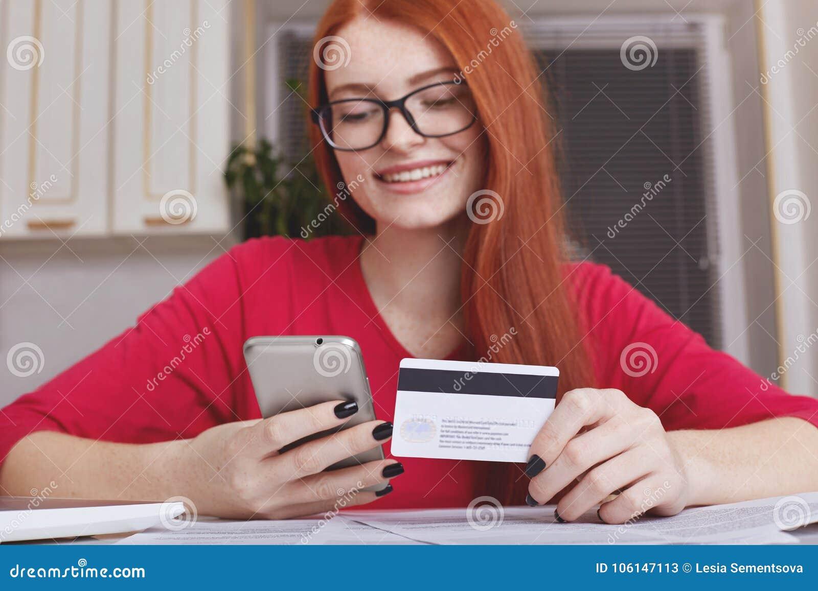 Redhaired vrij vrouwelijke model in eyewear houdt slimme telefoon en maakt de creditcard, online aankoop of het winkelen in Inter