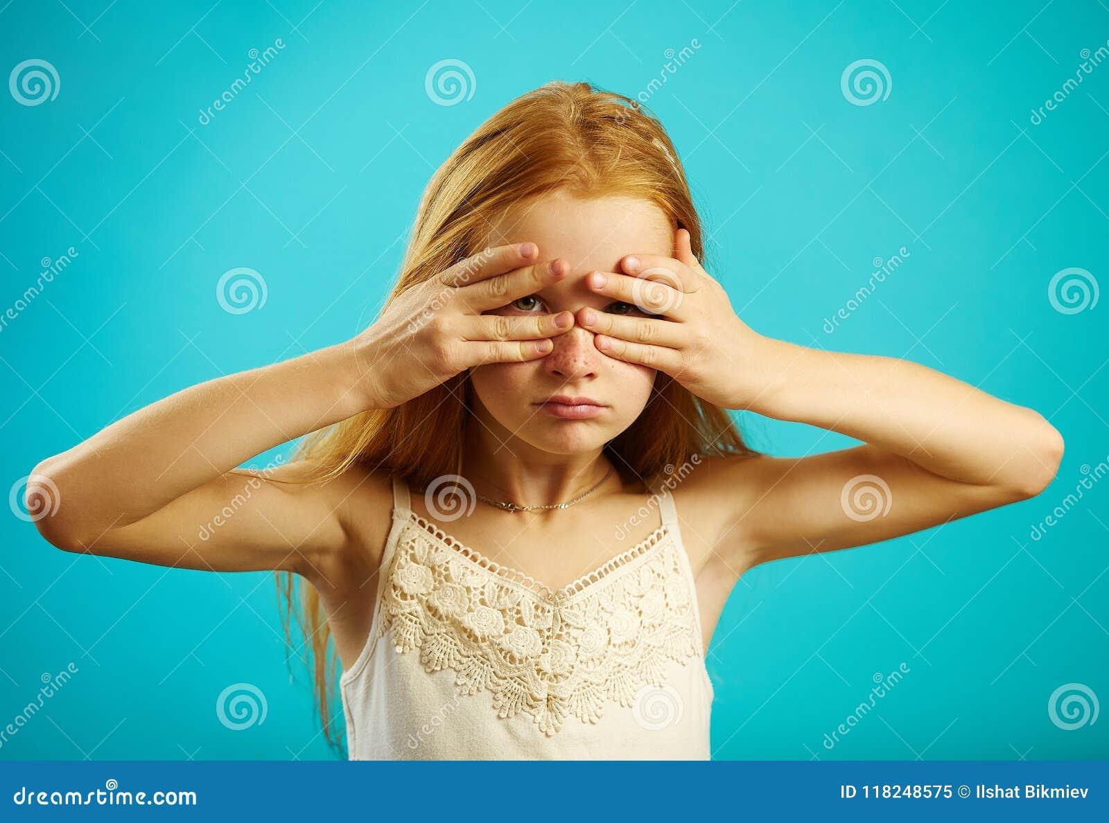 Redhead καλυμμένα κορίτσι μάτια με τα χέρια, που τιτιβίζουν μέσω των δάχτυλων
