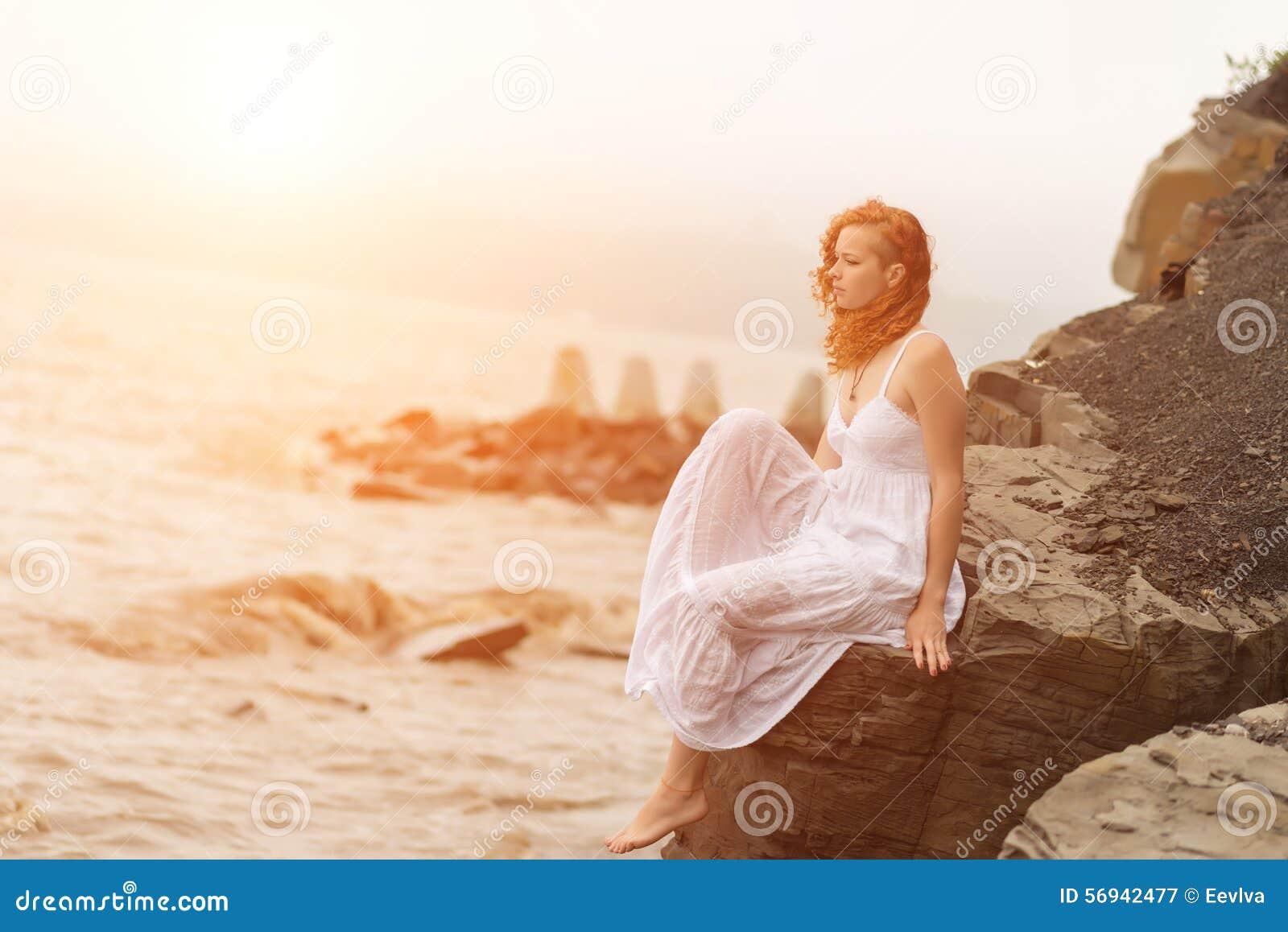 Redhead συνεδρίαση γυναικών στην ακτή στην παραλία