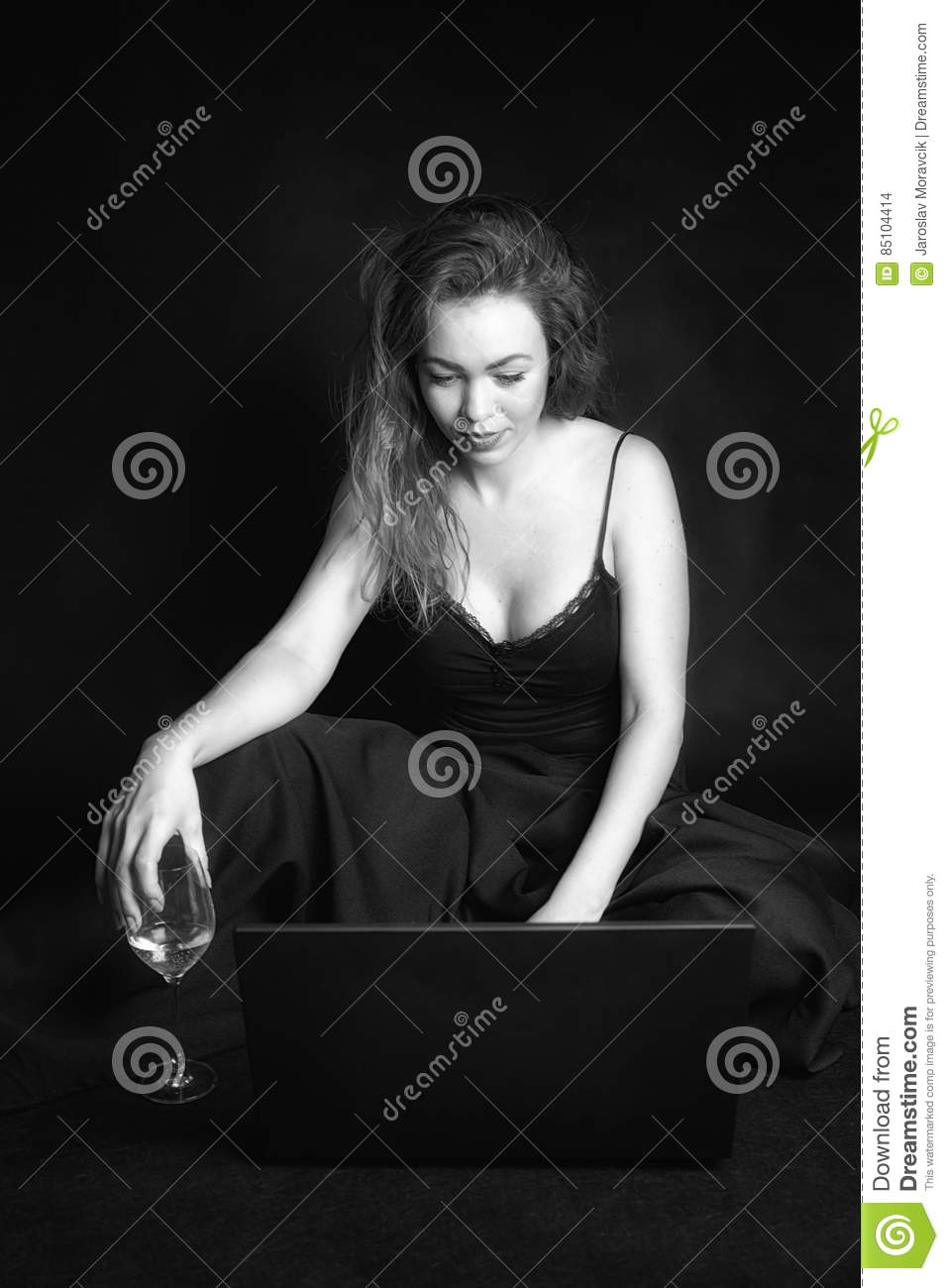Redhead girl with laptop and glass of wine