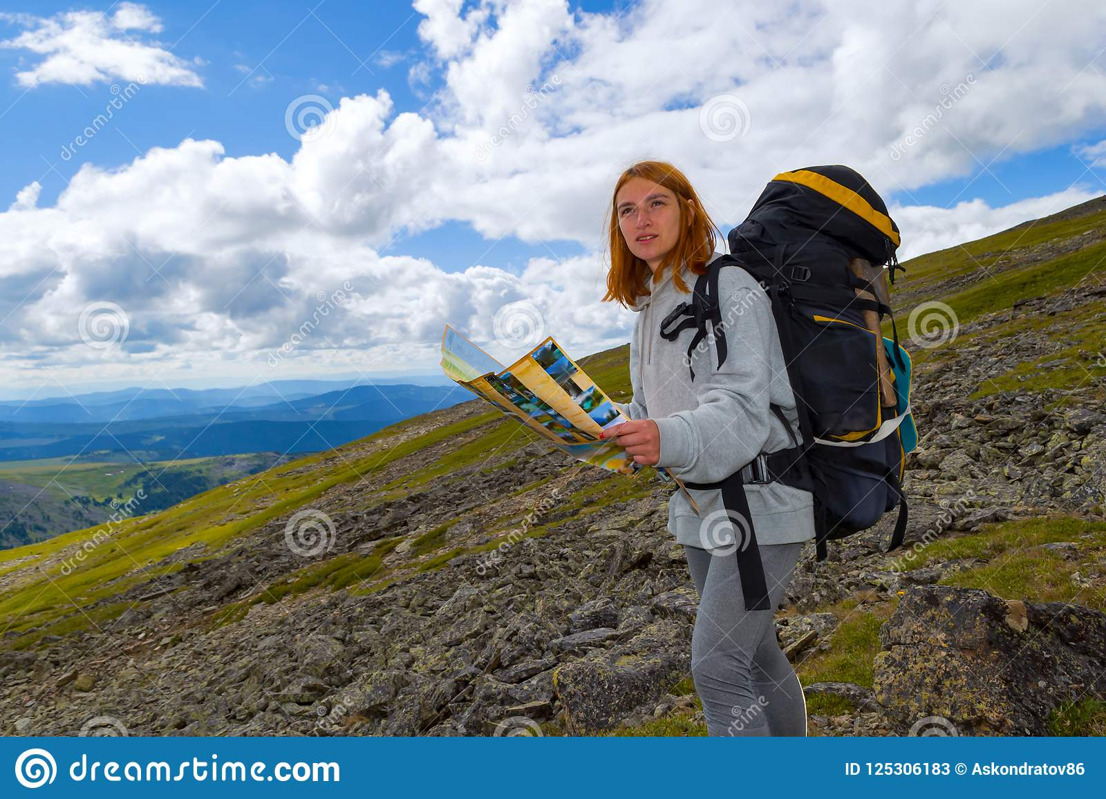 The redhead girl tourist makes a route on the map in her hands,