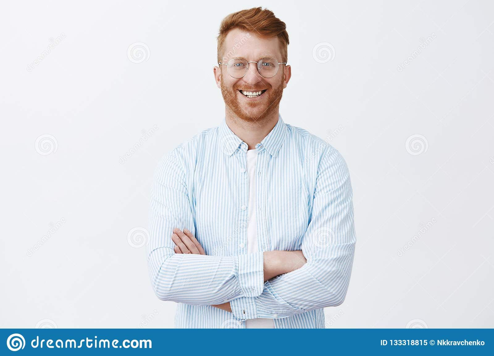 Redhead guy knows everything about business, standing in trendy shirt over gray wall with crossed hands on chest