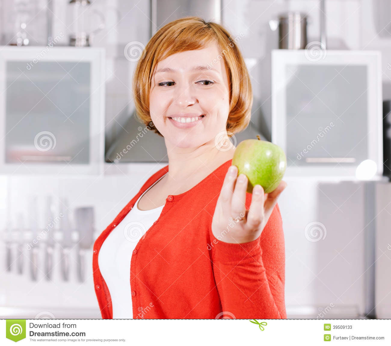 Redhead housewife with apple in kitchen