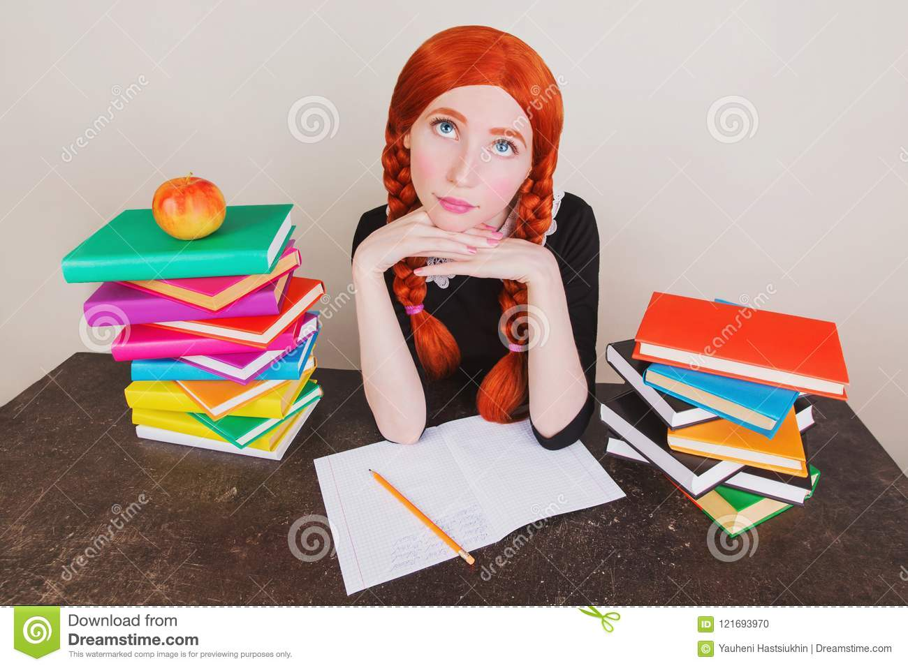 81a5f2e78381 Redhead schoolgirl in school uniform sits at desk on gray background.  Colored text books on table. The apple lies on book.