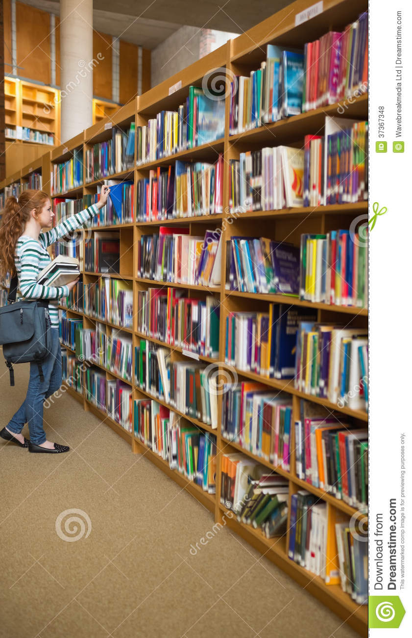 Redhead Student Taking A Book From Bookshelf In The Library Download Preview