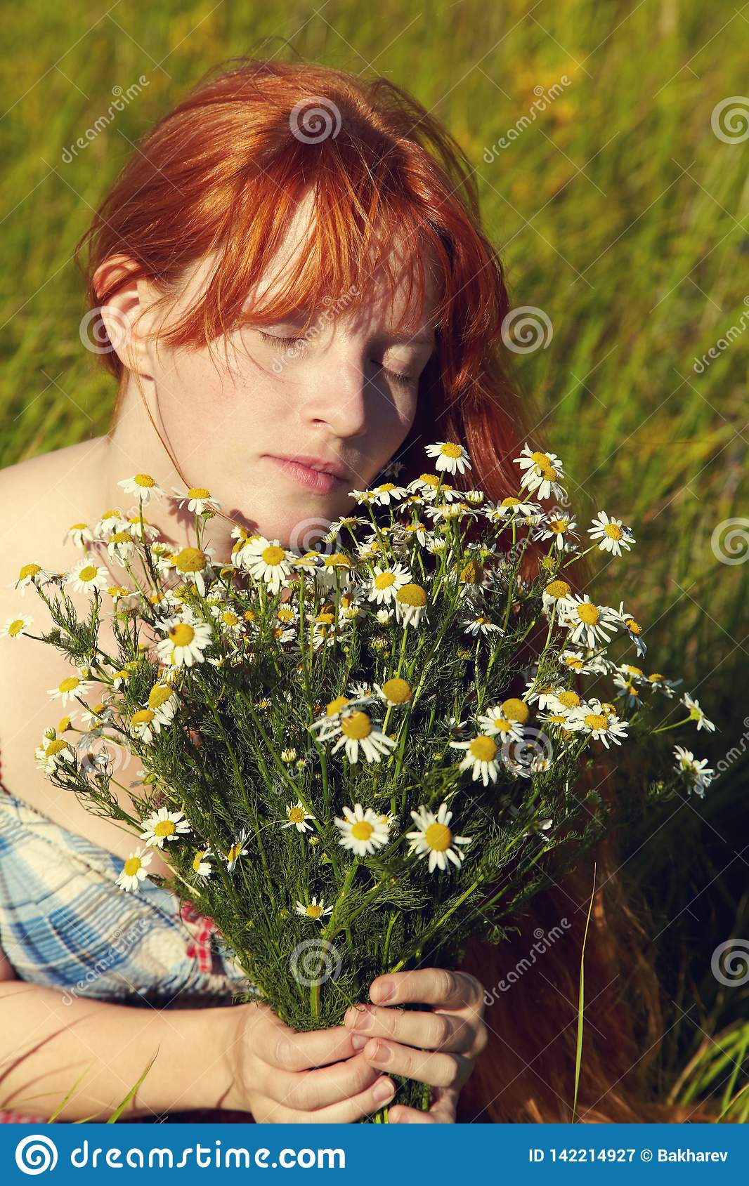 Redhead woman with a bouquet of flowers in a dress outdoors. stylish romantic young girl in field