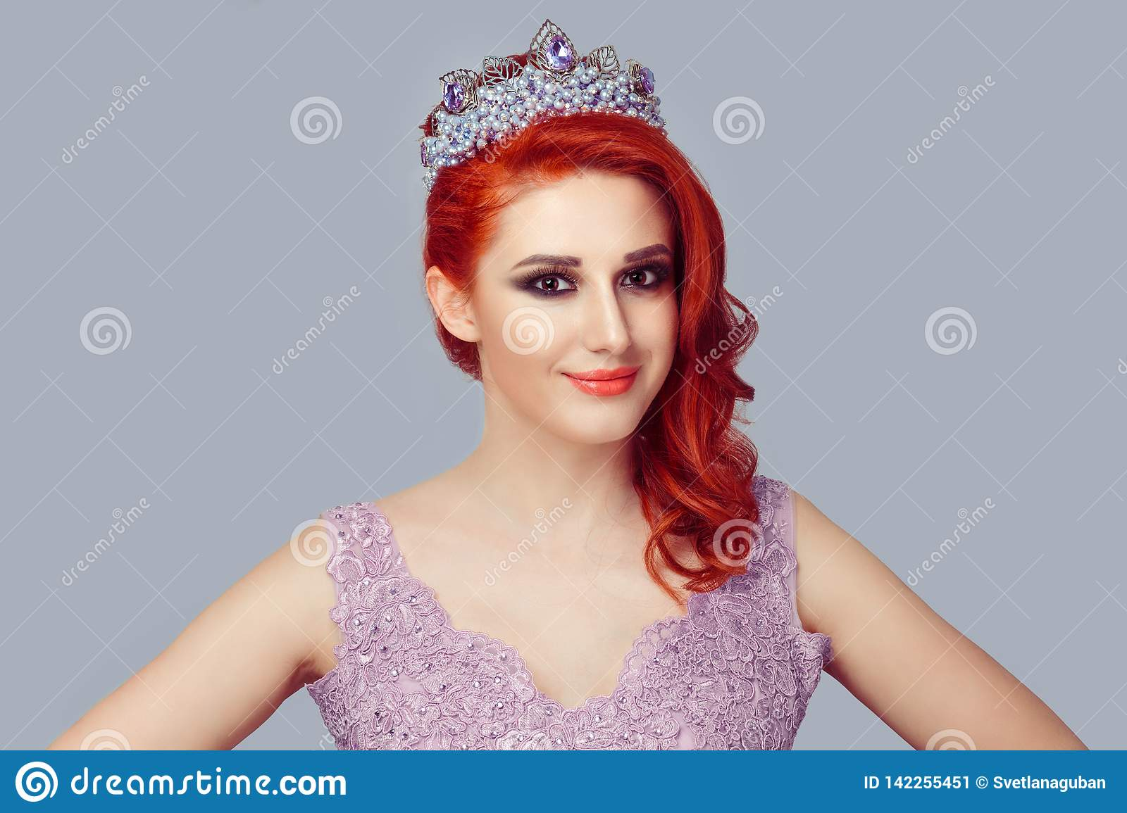 Redhead woman in crown with purple pearls and crystals in violet color lace dress
