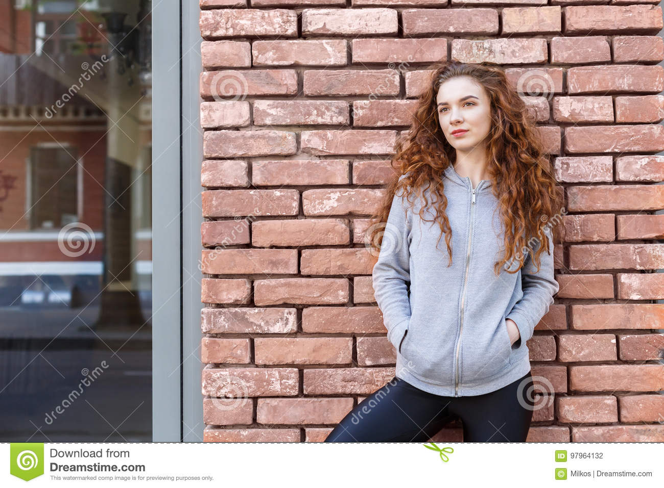 Pensive redhead woman leaning on brick wall, relaxing from jog training,  copy space