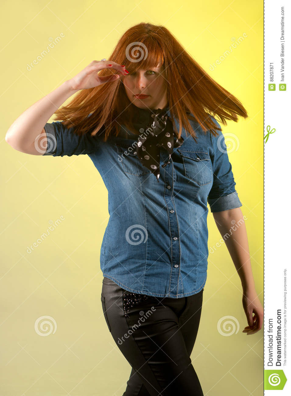 332b734f2acff Redhead woman looking suspicious wearing a blue jeans shirt and black  leather trousers with long hair waving due to her turn looking in the  camera on a ...