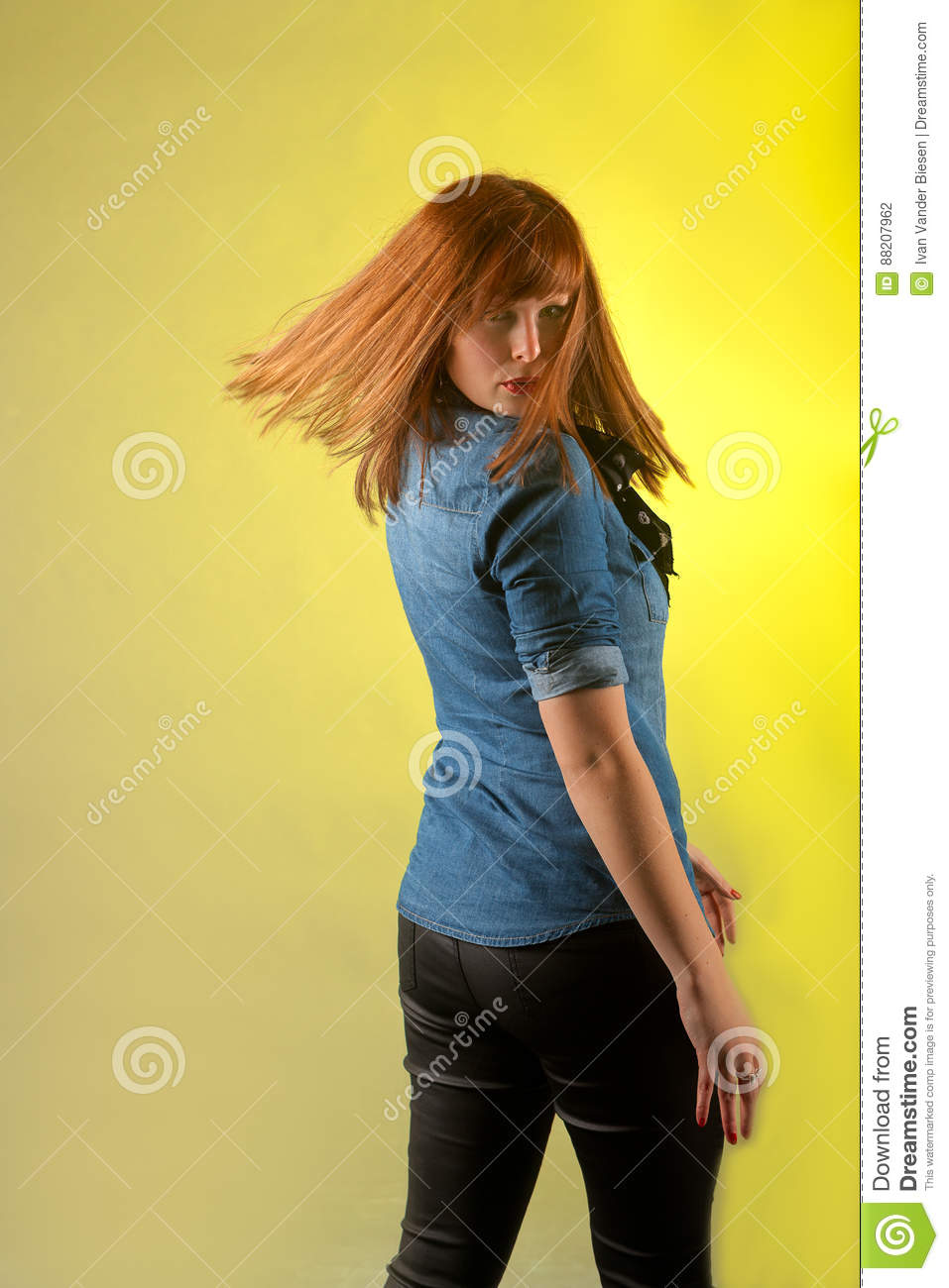1be62f80512f1 Redhead woman turning from the back looking looking in the camera wearing a  blue jeans shirt and black leather trousers on a yellowish background.