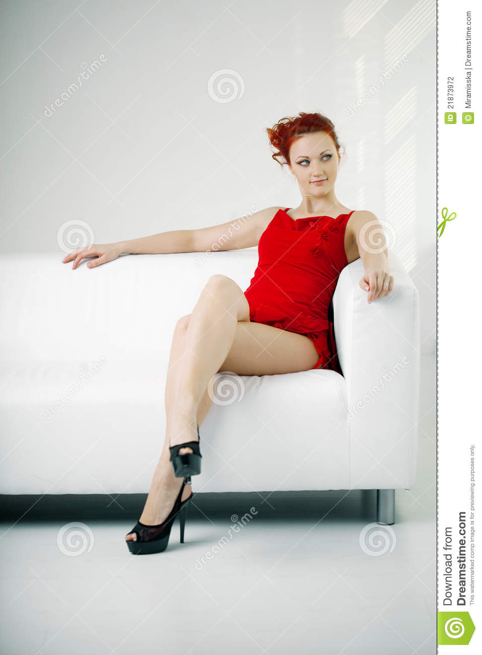 Redhead Woman In A Red Dress On White Couch Stock Photo