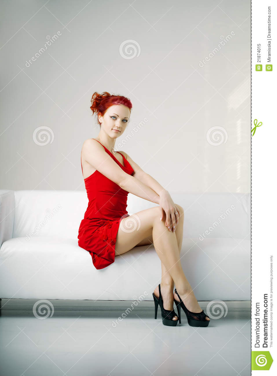 Redhead Woman In A Red Dress On White Couch Royalty Free