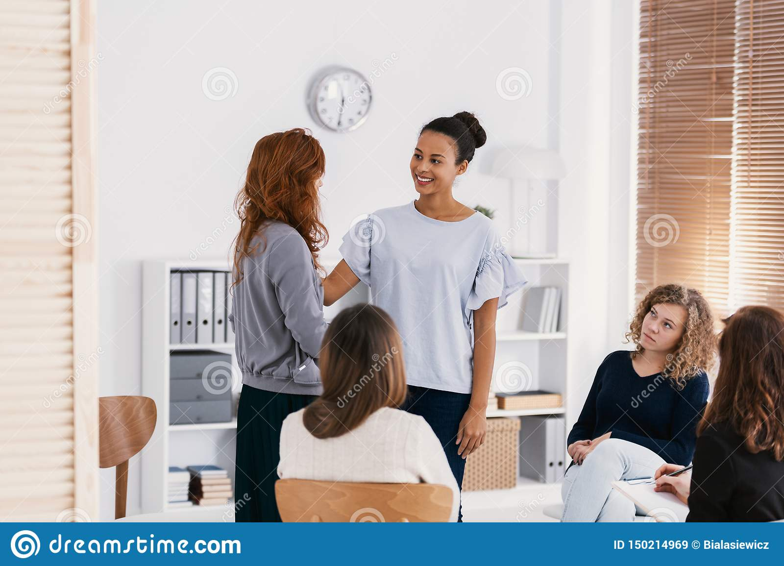 Redhead woman supporting sad friend during psychotherapy group meeting