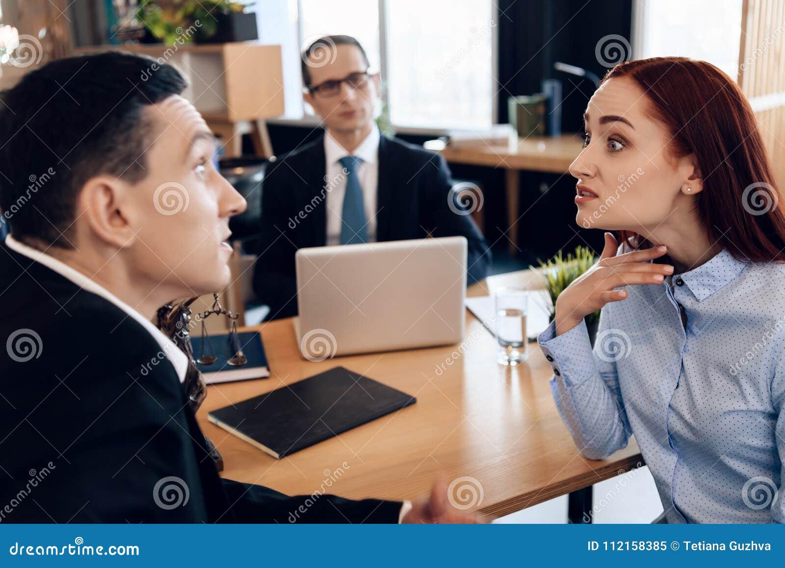Redheaded сердитая женщина спорит с взрослым человеком в офисе ` s юриста развода