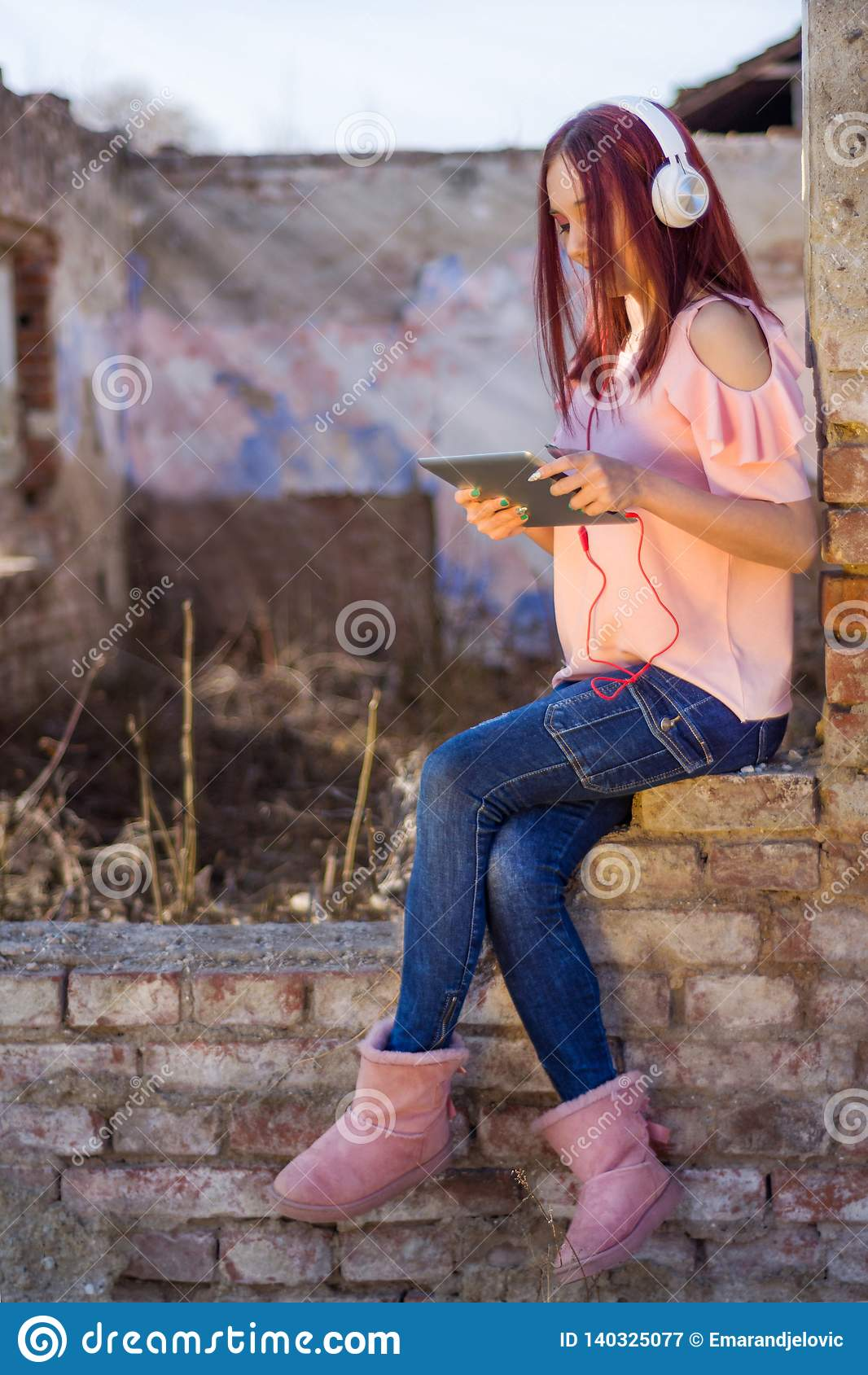 Redheads lady with digital tablet listening to music on headphones on ruins wall bricks of retro house in sunset