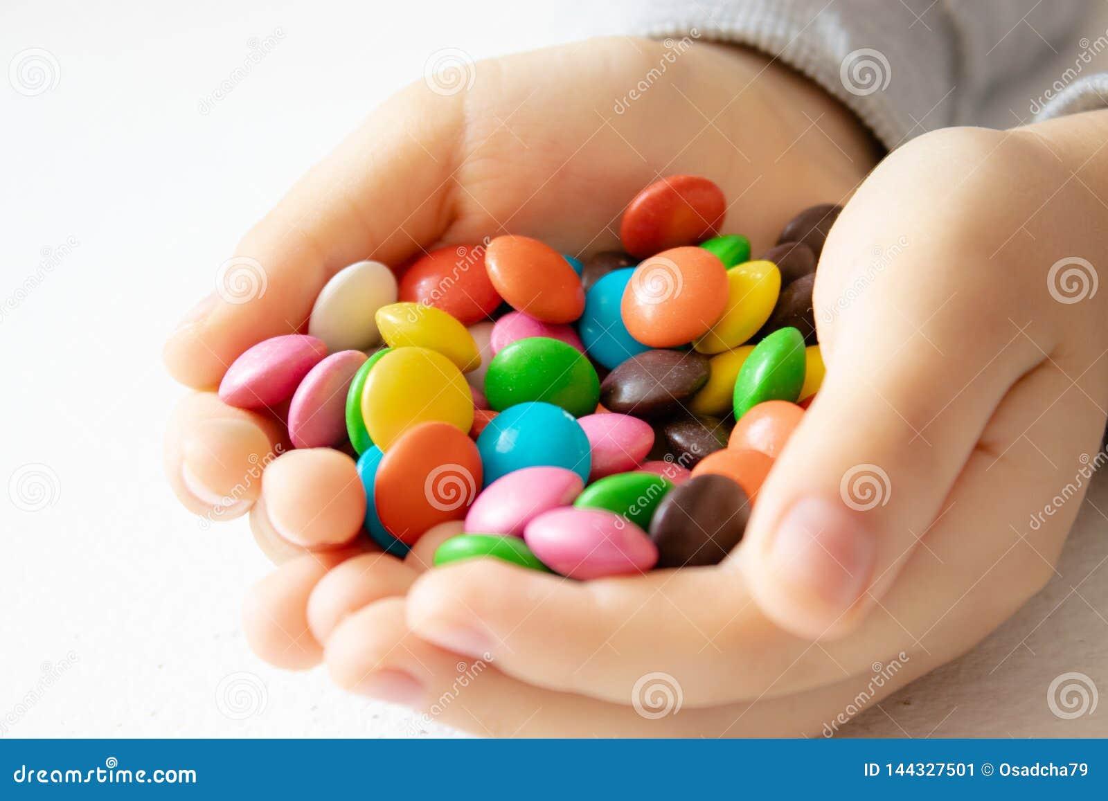 Redondo, multi-colorido, chocolates Uma pilha de doces multi-coloridos Uma criança guarda uns doces