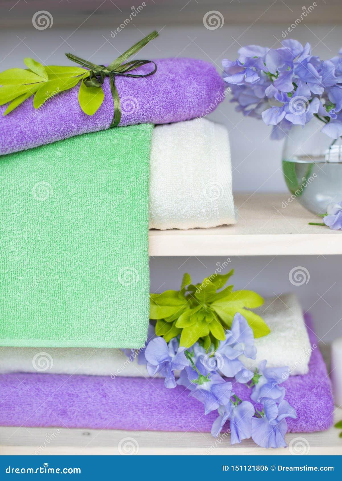 Reeks de verschillende handdoeken van de kleurenbadstof met blauwe bloemen en kaarsen op houten shelfs