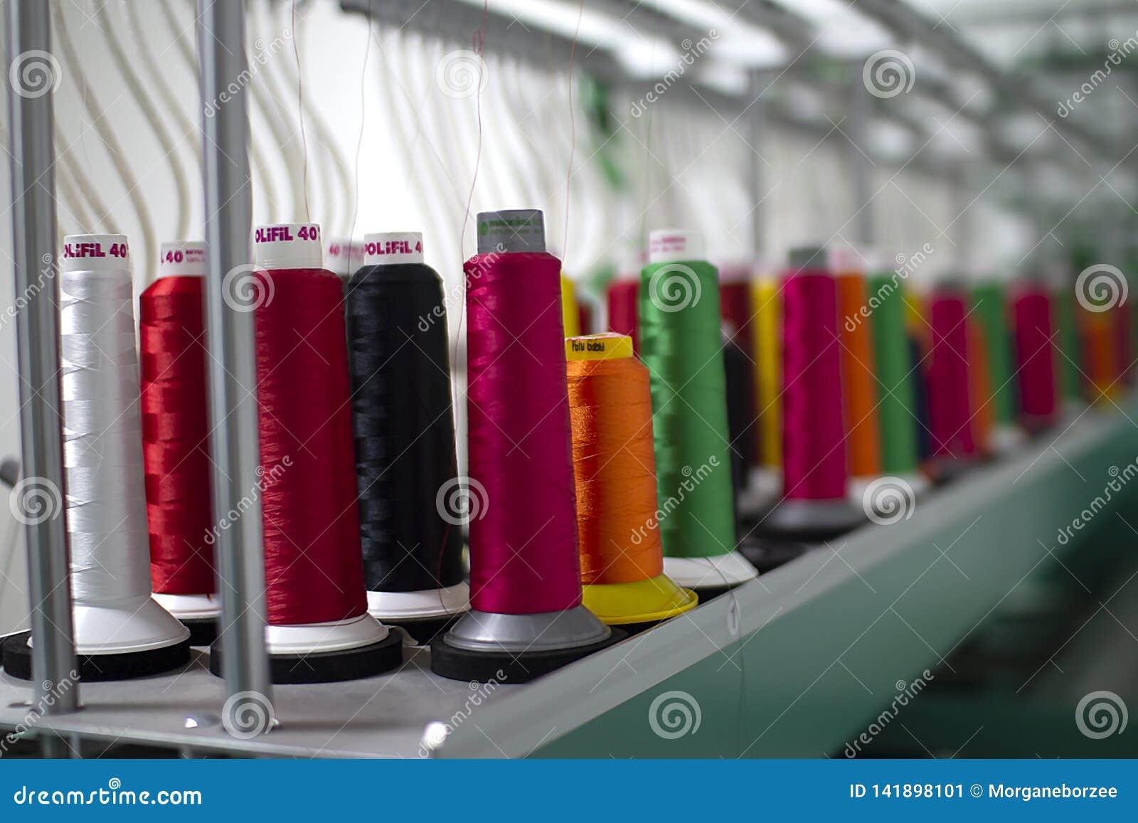 Reeks gekleurde draden voor het naaien op rollen