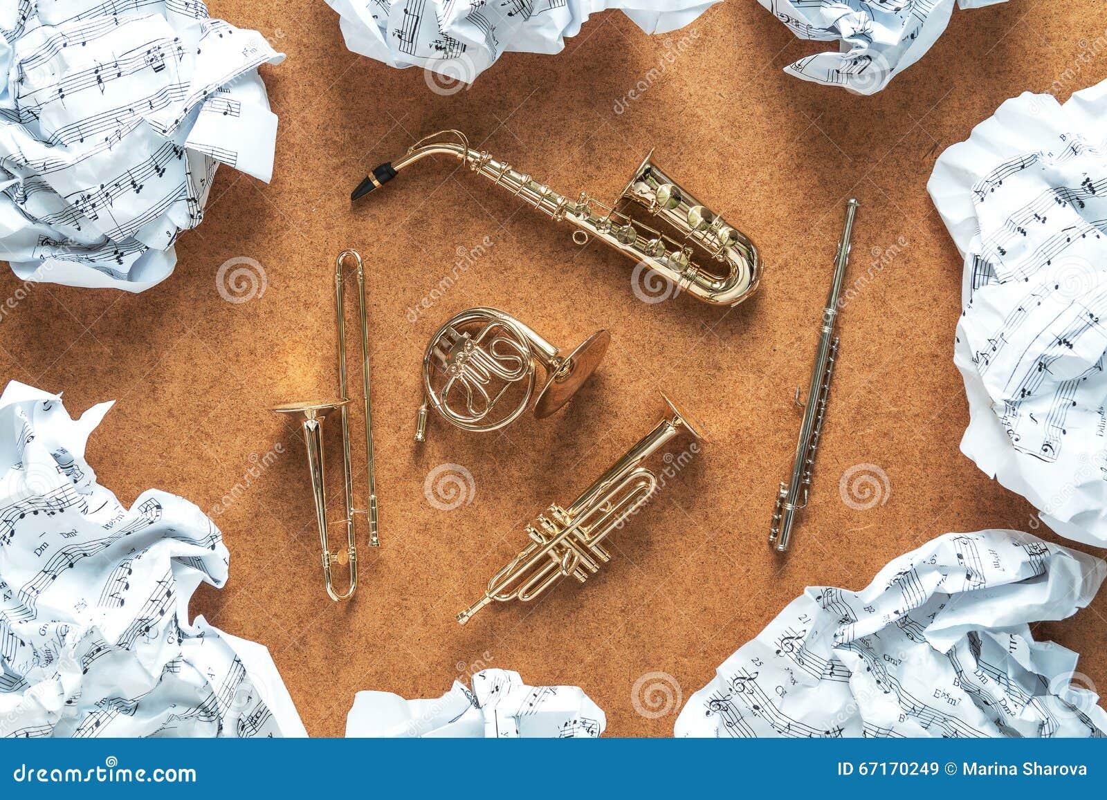 Reeks gouden stuk speelgoed het orkestinstrumenten van de messingswind: saxofoon, trompet, Franse hoorn, trombone Het concept van