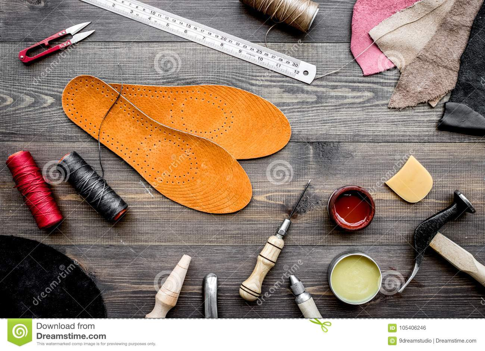Reeks schoenmakershulpmiddelen op bruine houten bureau hoogste mening als achtergrond