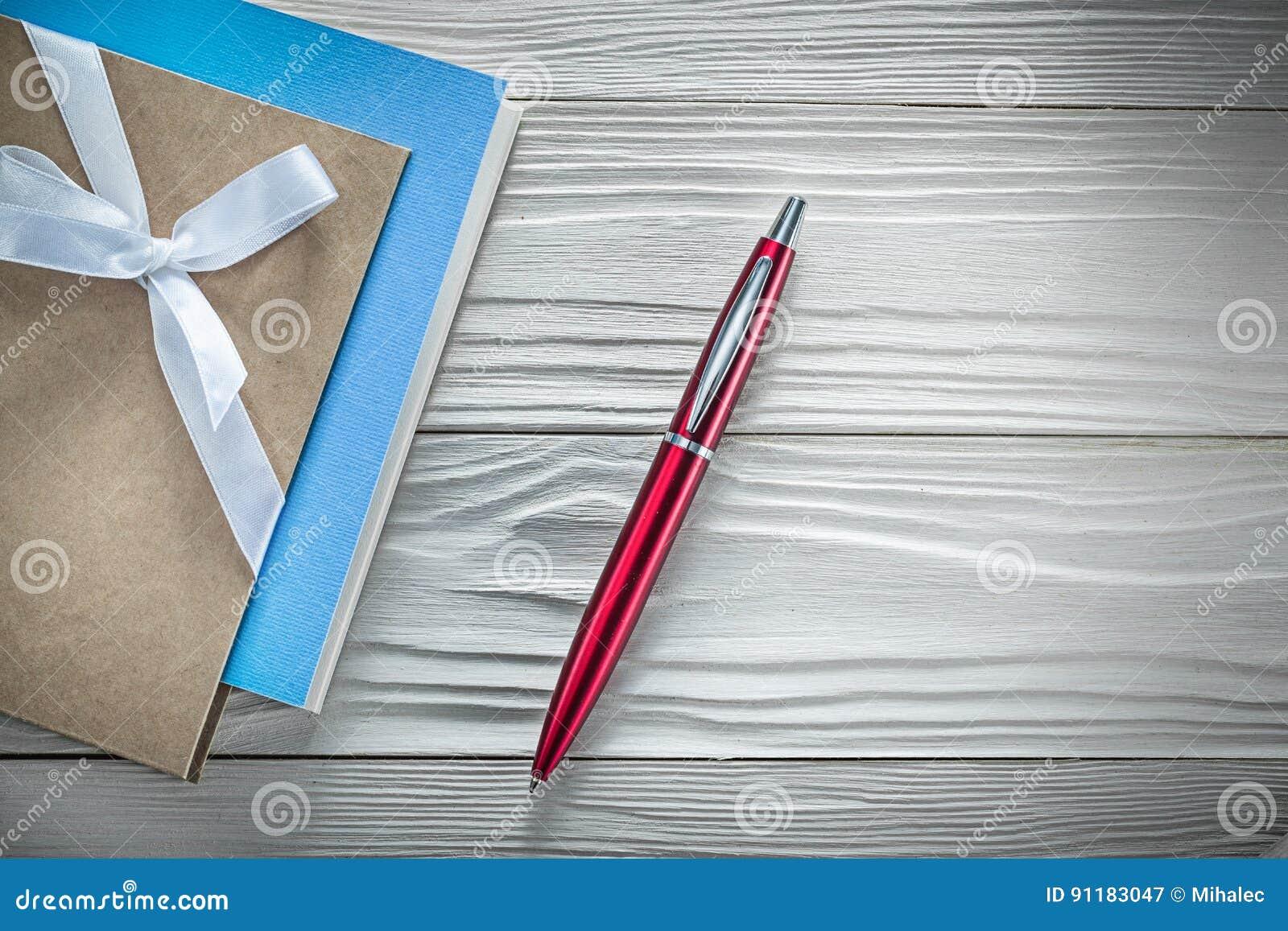 Reeks van de uitstekende pen van blocnotes rode biro op houten raad direct ab