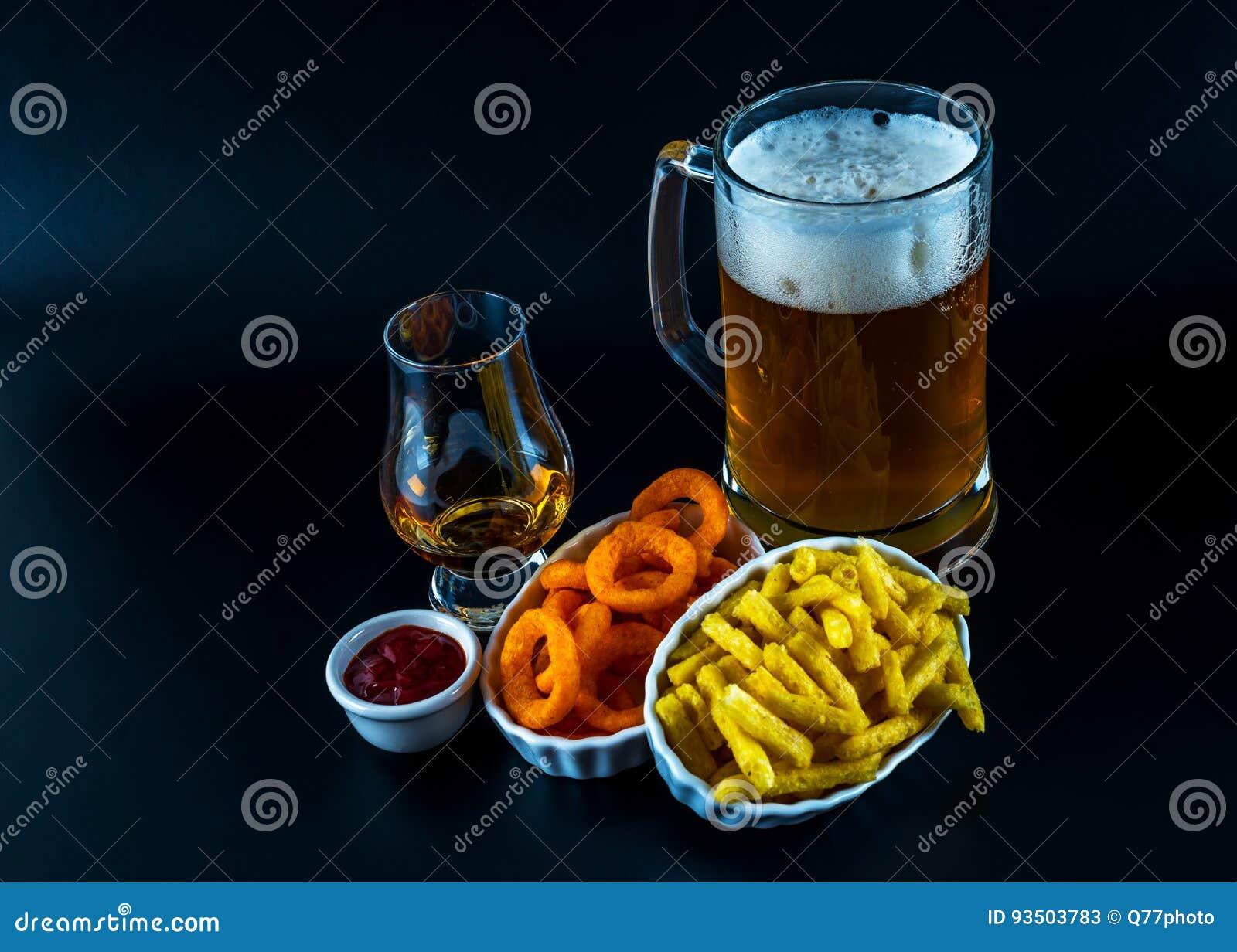 Reeks van snacks met verschillende onderdompelingen, enig mout in een glas en pi