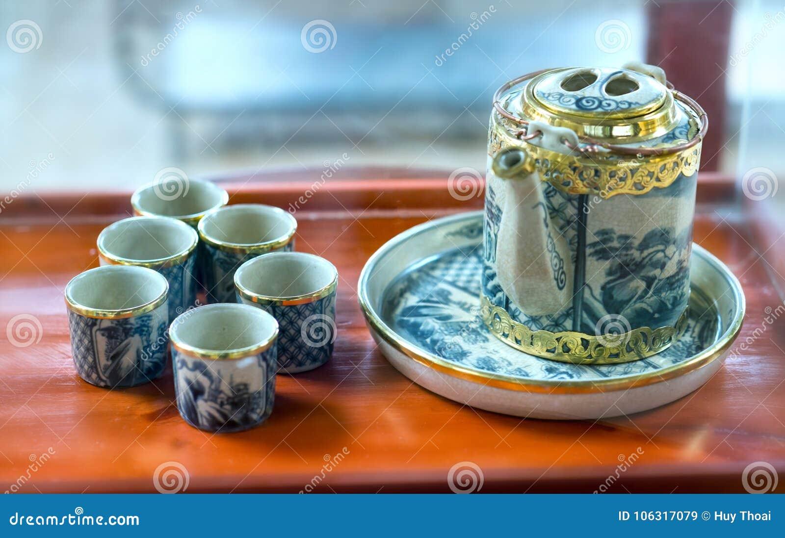 Reeks van theepotten en de oude theekop op de lijst