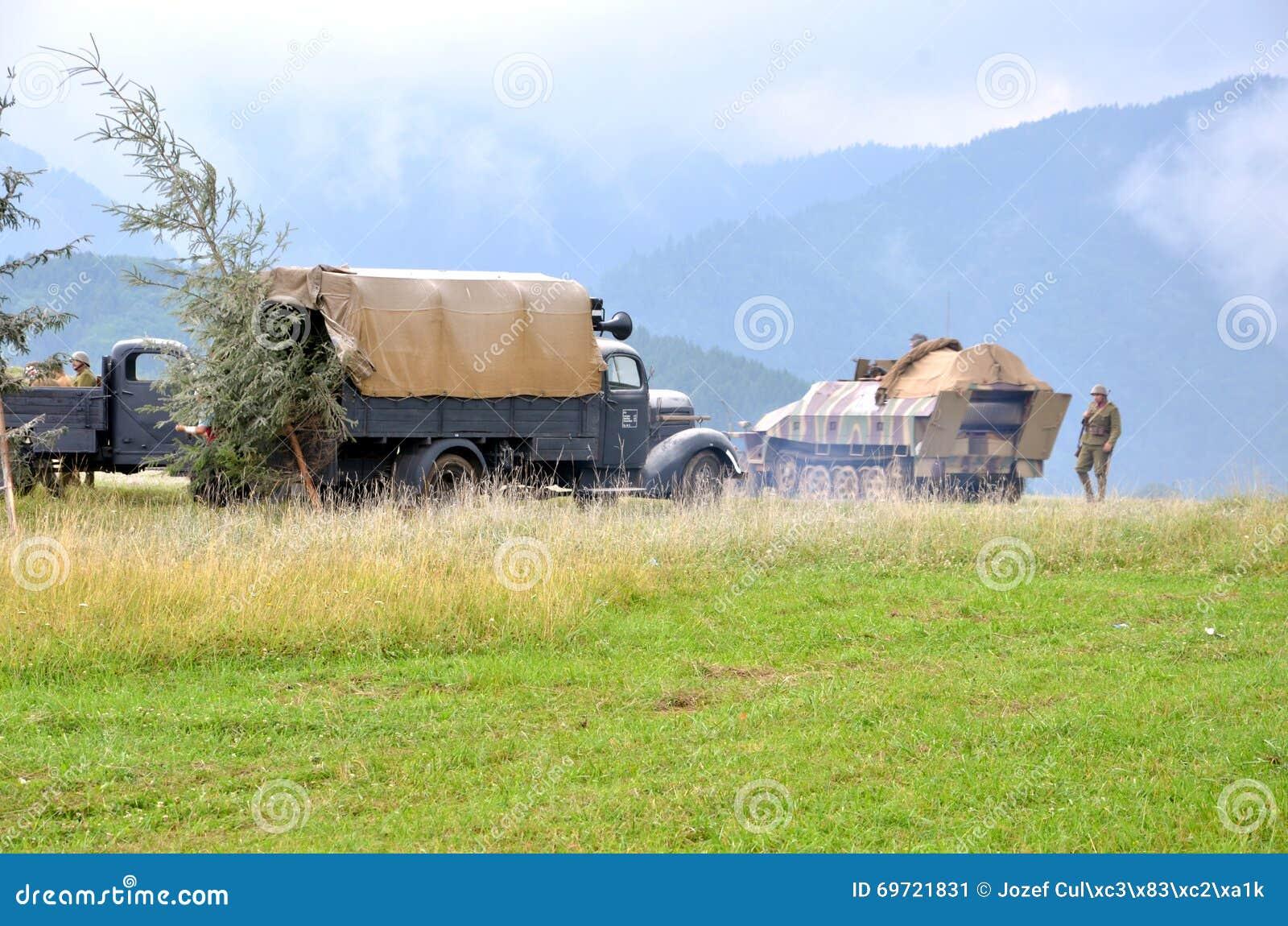 Reenactment histórico da batalha da guerra mundial 2 - o veículo e os soldados blindados de transporte vestiram-se em uniformes a