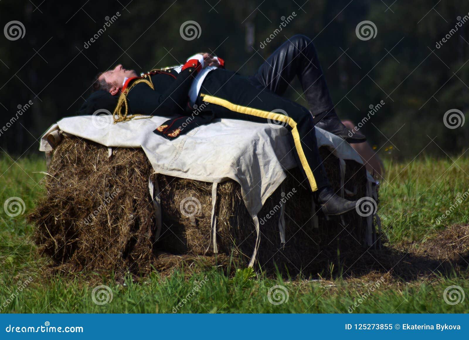 Reenactor se repose sur le cube de foins à la reconstitution historique de bataille de Borodino en Russie