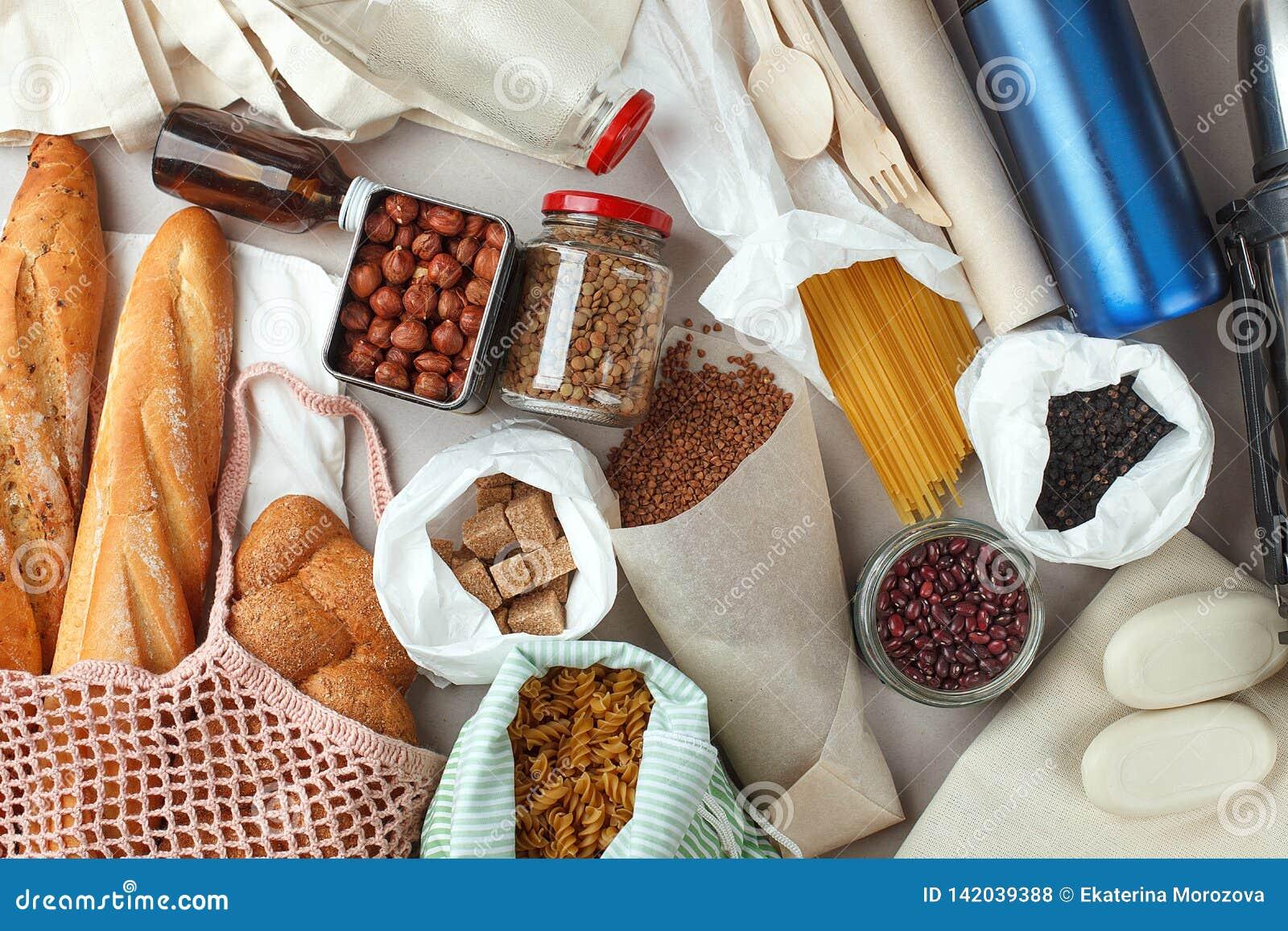 Refeição nos sacos, no vidro e no papel do algodão do eco empacotando na tabela na cozinha do mercado Conceito waste zero da comp