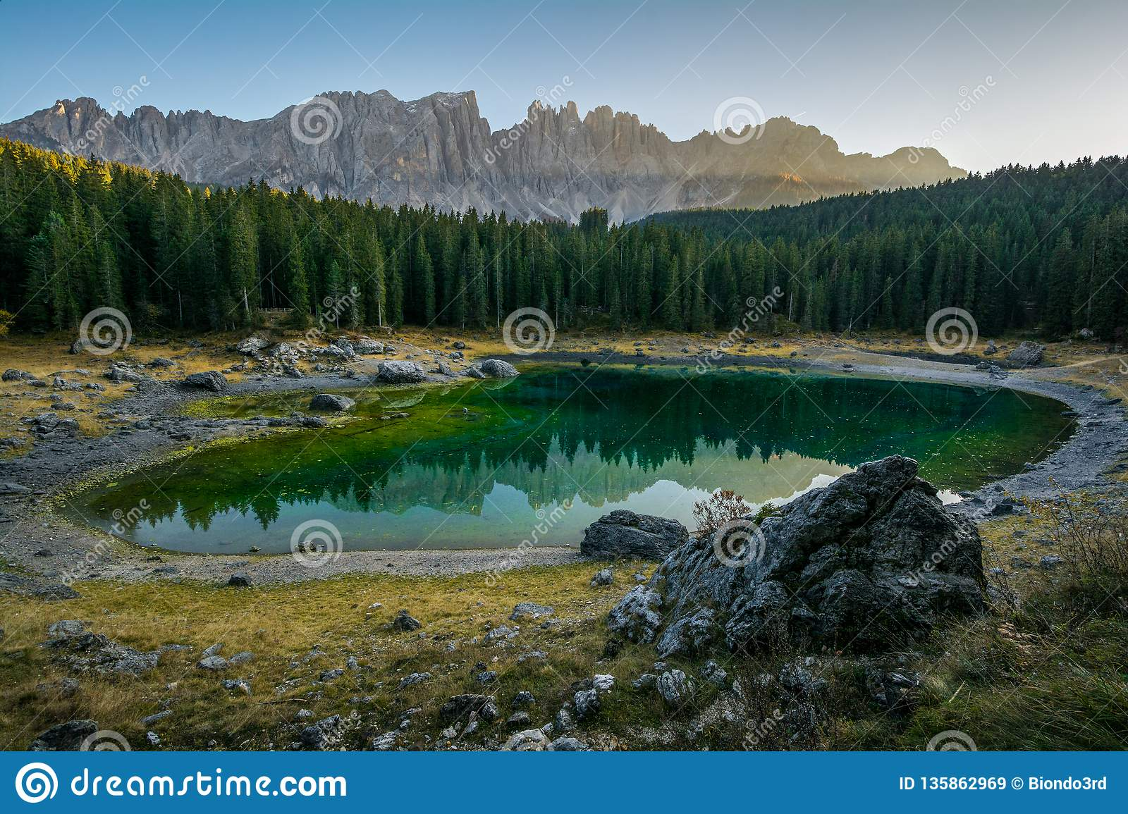 Reflection of Latemar in the clear water of Lake Carezza Karersee in Dolomite Alps, Trentino Alto Adige, South Tirol, Italy