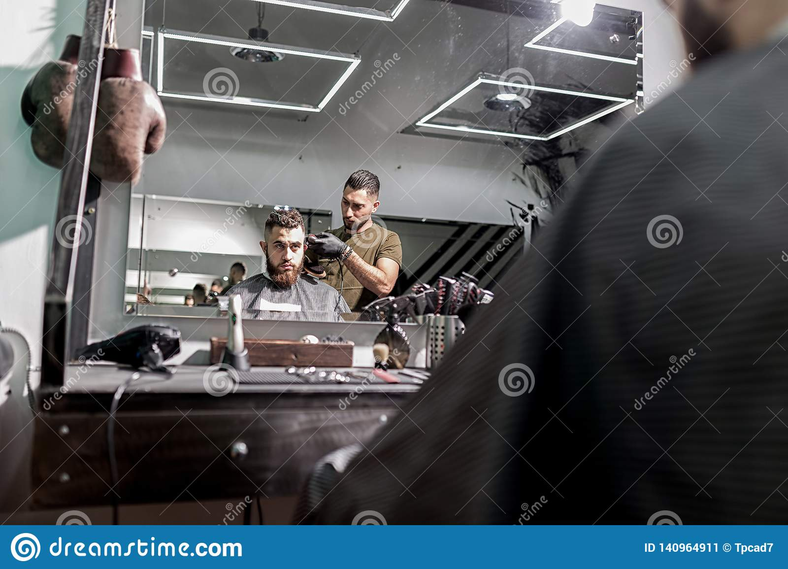 Reflection in the mirror of brutal man sits in a chair and barber shaves his hairs.