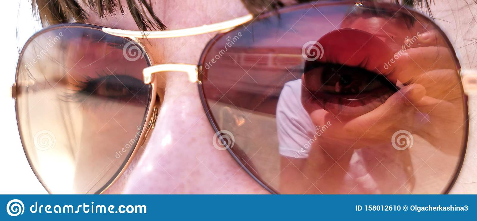 Reflection of a photographer in sunglasses of a young attractive woman, close-up