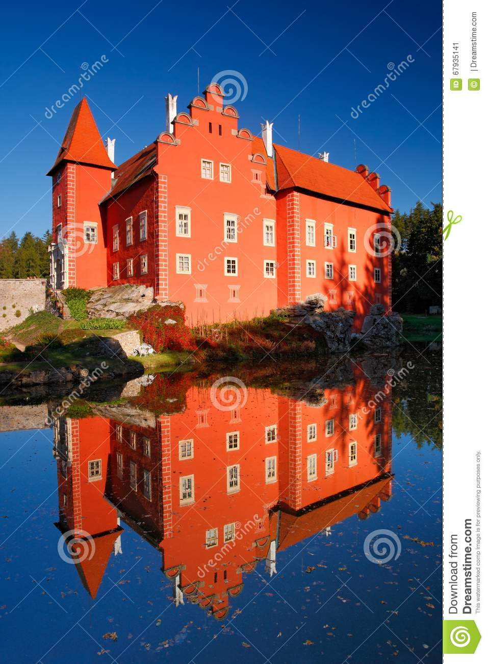Reflection of the red castle on the lake, with dark blue sky, state castle Cervena Lhota, Czech republic