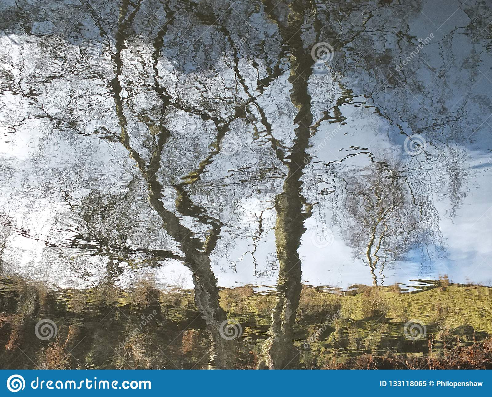 Reflection of a tree and hillside blurred by rippling water with blue cloudy sky