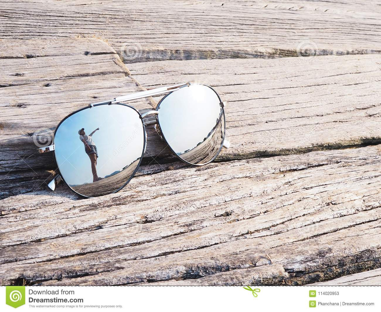 Reflection of woman hand pointing upward to blue sky in sunglasses