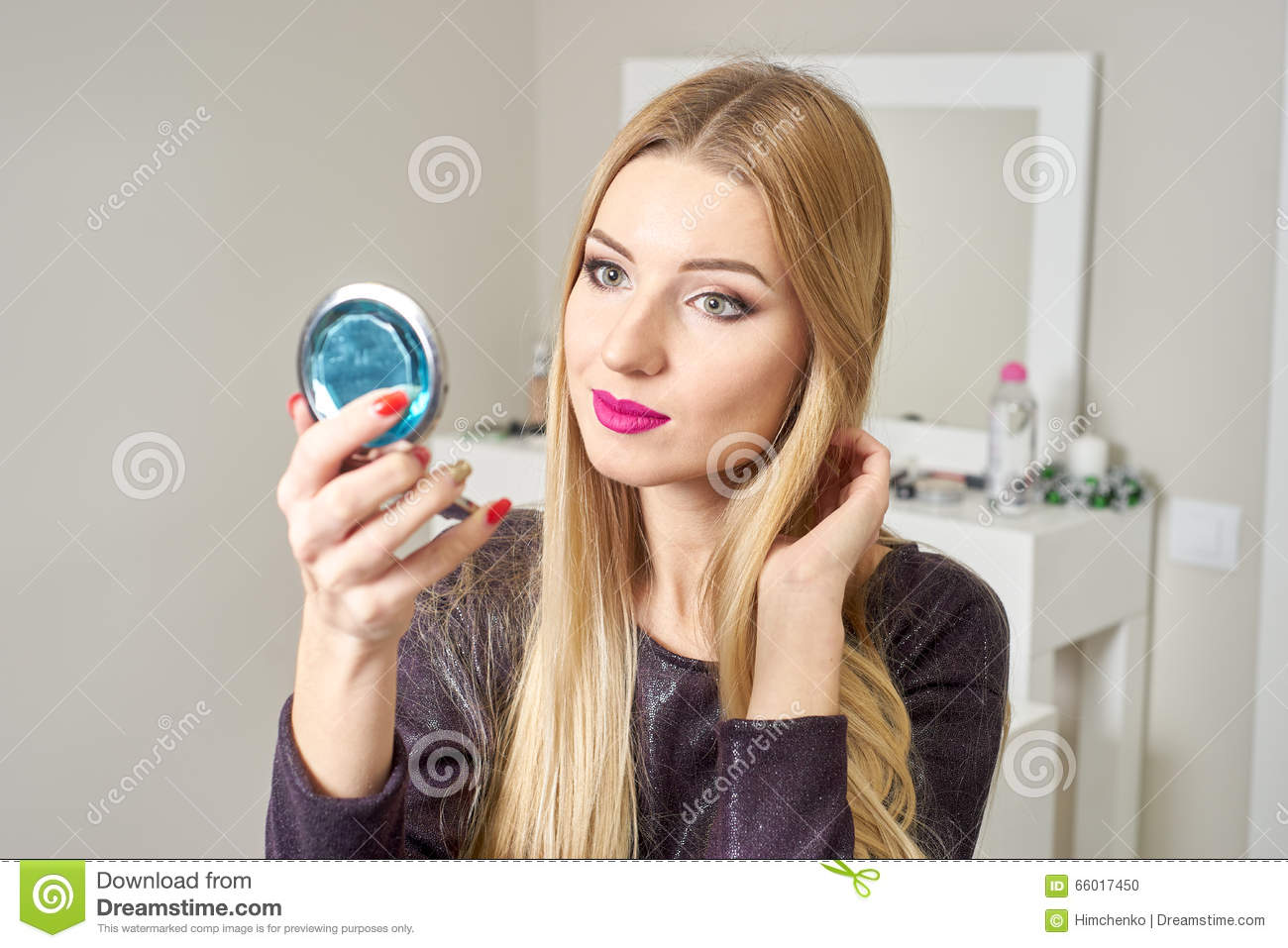 Reflection Of Young Beautiful Woman Applying Her Make Up