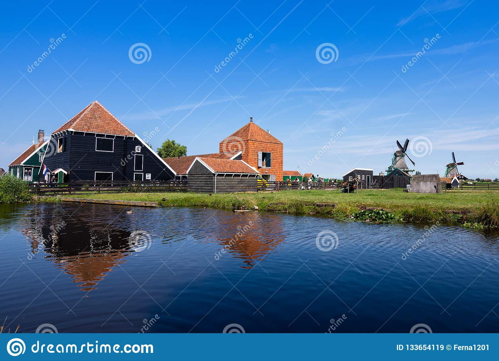 Reflections in the water of the farms and windmills on a lovely day, with a blue sky. Zaanse Schans. Holland