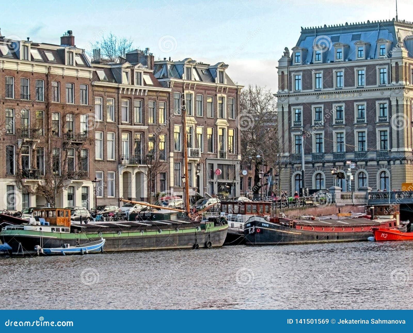 Reflexão de construções de tijolo flamengas tradicionais holandesas famosas de Amsterdão, canal da cidade na Holanda, Países Baix