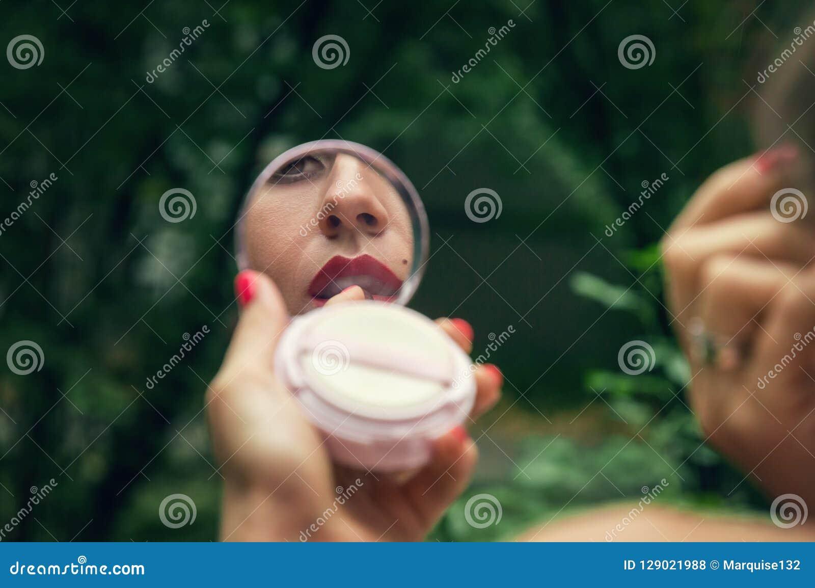 Reflexão do bordos em um espelho do estojo compacto, que a tintura da menina com batom vermelho Um parque verde em um fundo