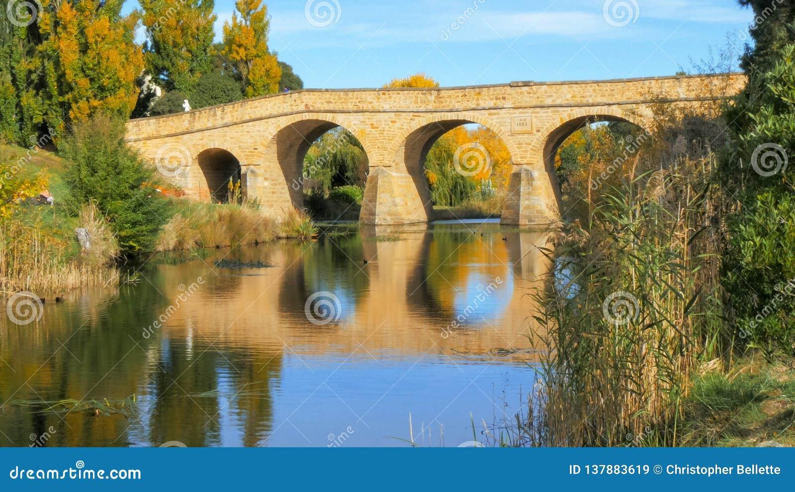 Reflexões da ponte de pedra velha histórica nas águas do rio de carvão