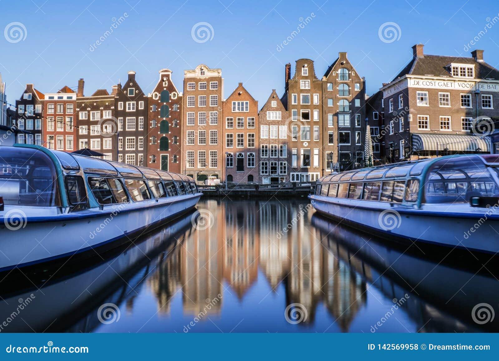 Reflexões de casas e de barcos de canal holandeses tradicionais do turista