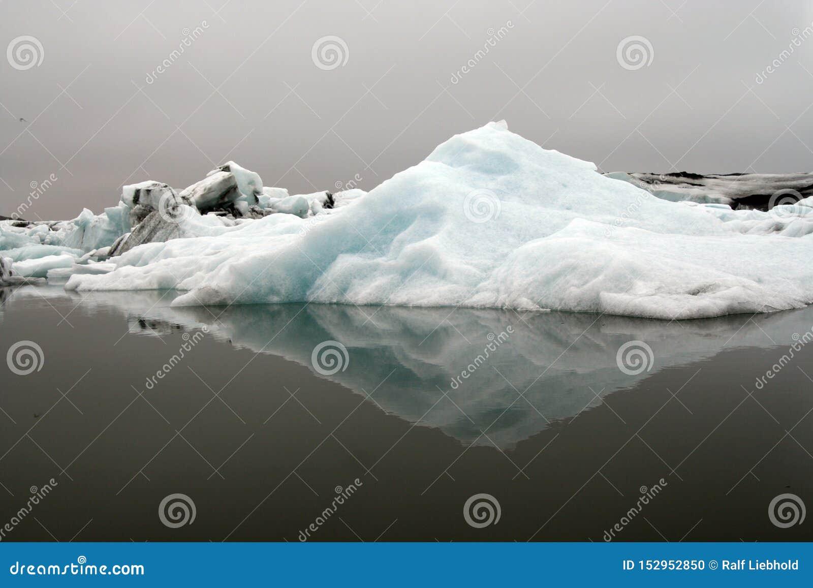 Reflexões dos icerbergs azuis e brancos de cristal na água escura preta na luz sombrio não ofuscante - geleira de Jökulsárlón Jok