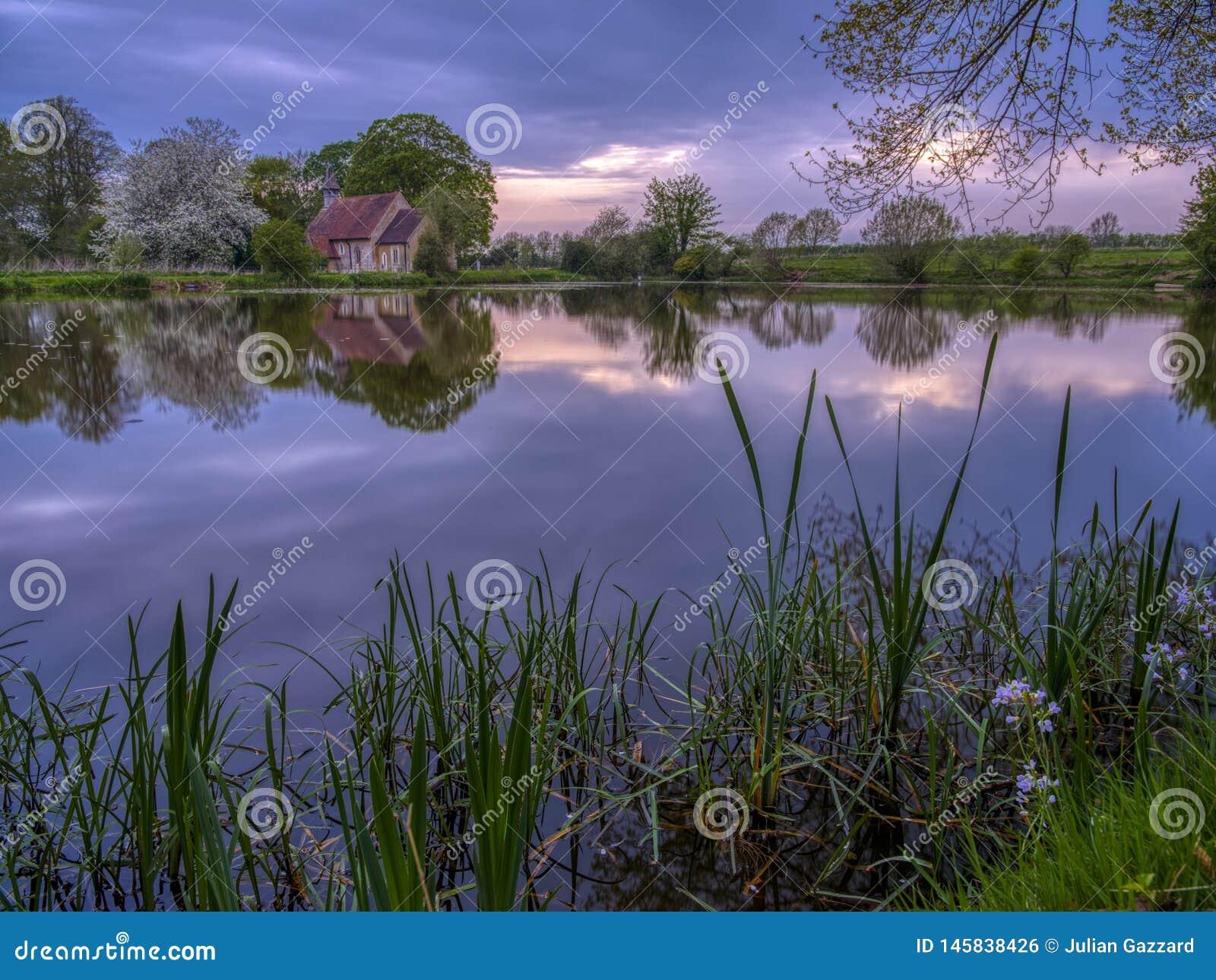 Reflex?es da igreja de St Leonard em Hartley Mauditt Pond, penas sul parque nacional, Reino Unido