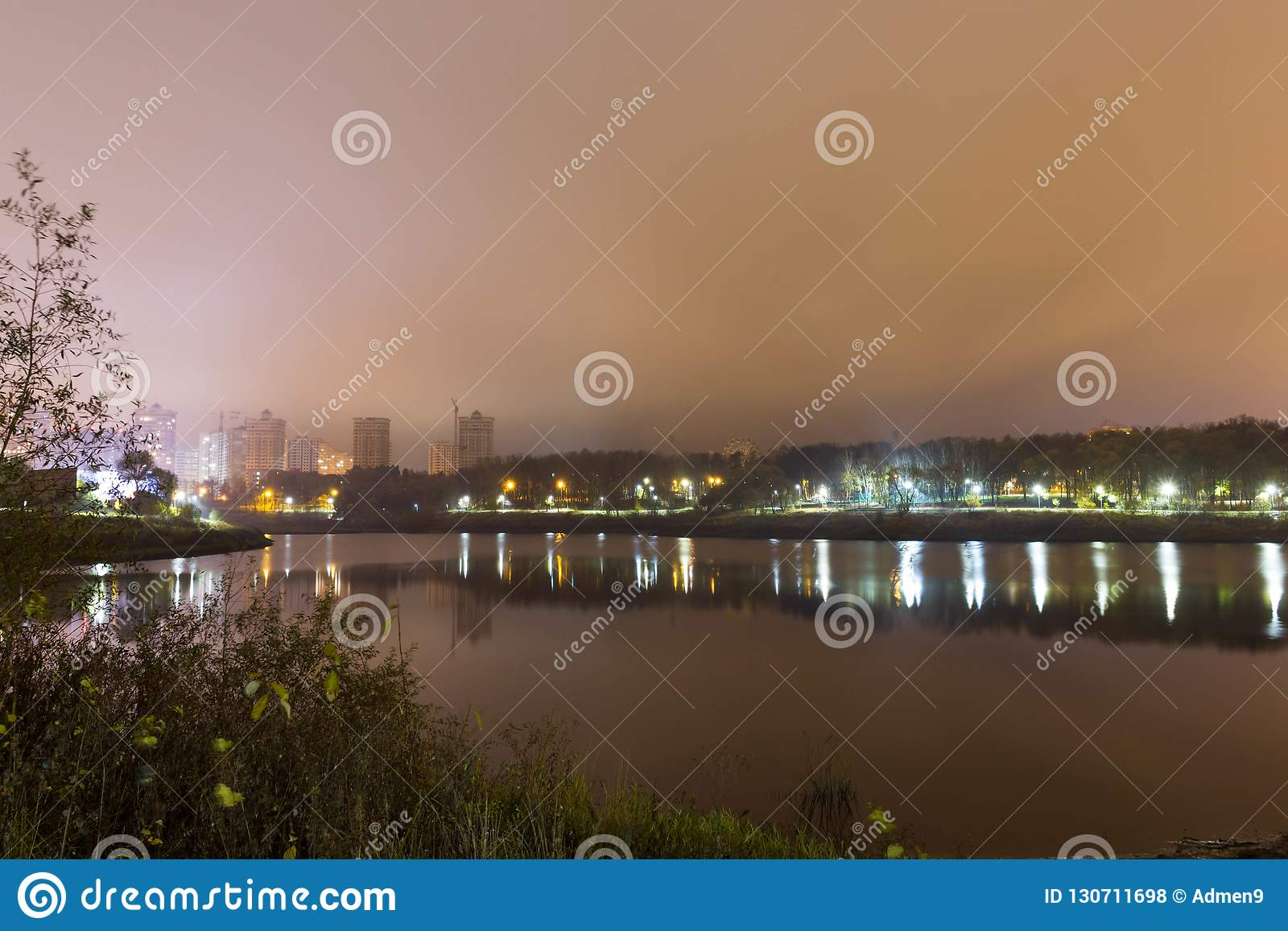 Reflexión de la ciudad con las luces de la noche en el lago