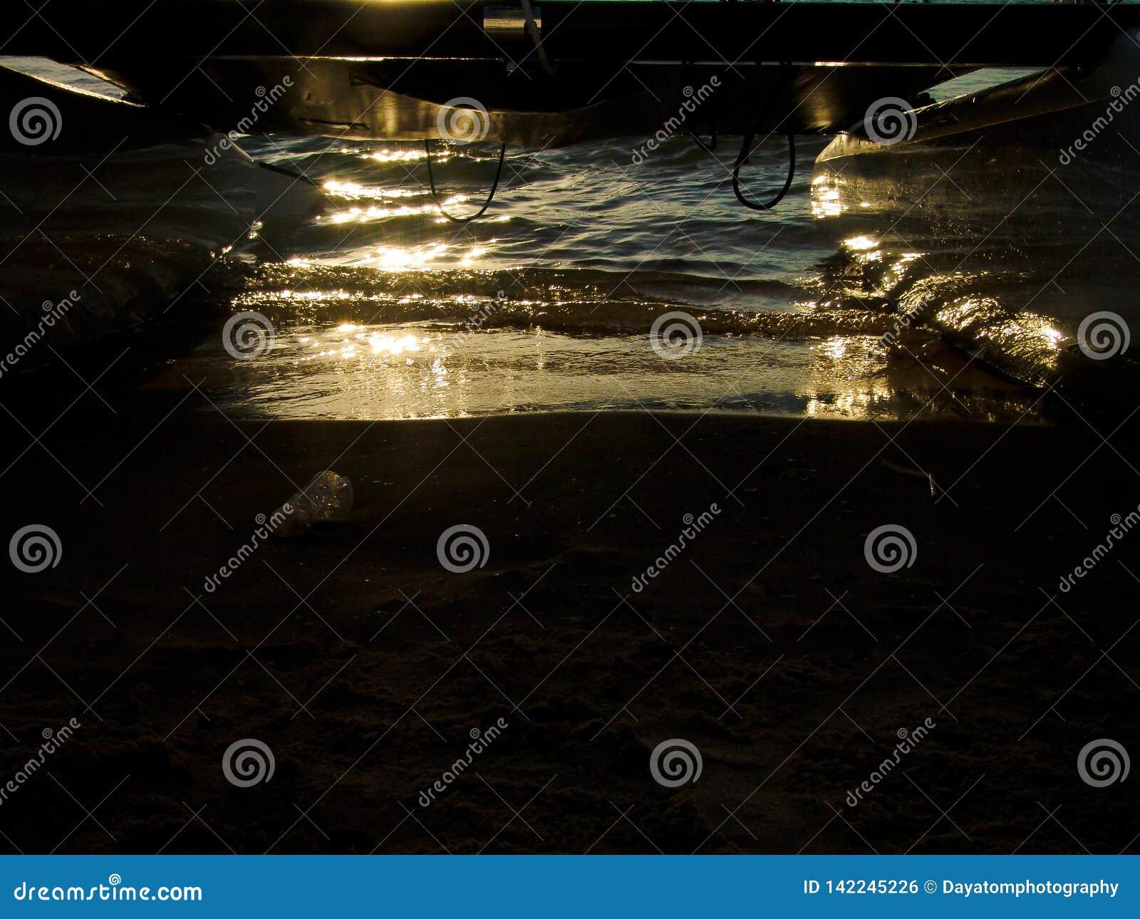 Reflexión de la puesta del sol en la arena mojada sobre una playa arenosa en el océano, debajo de un barco del tablero de resaca