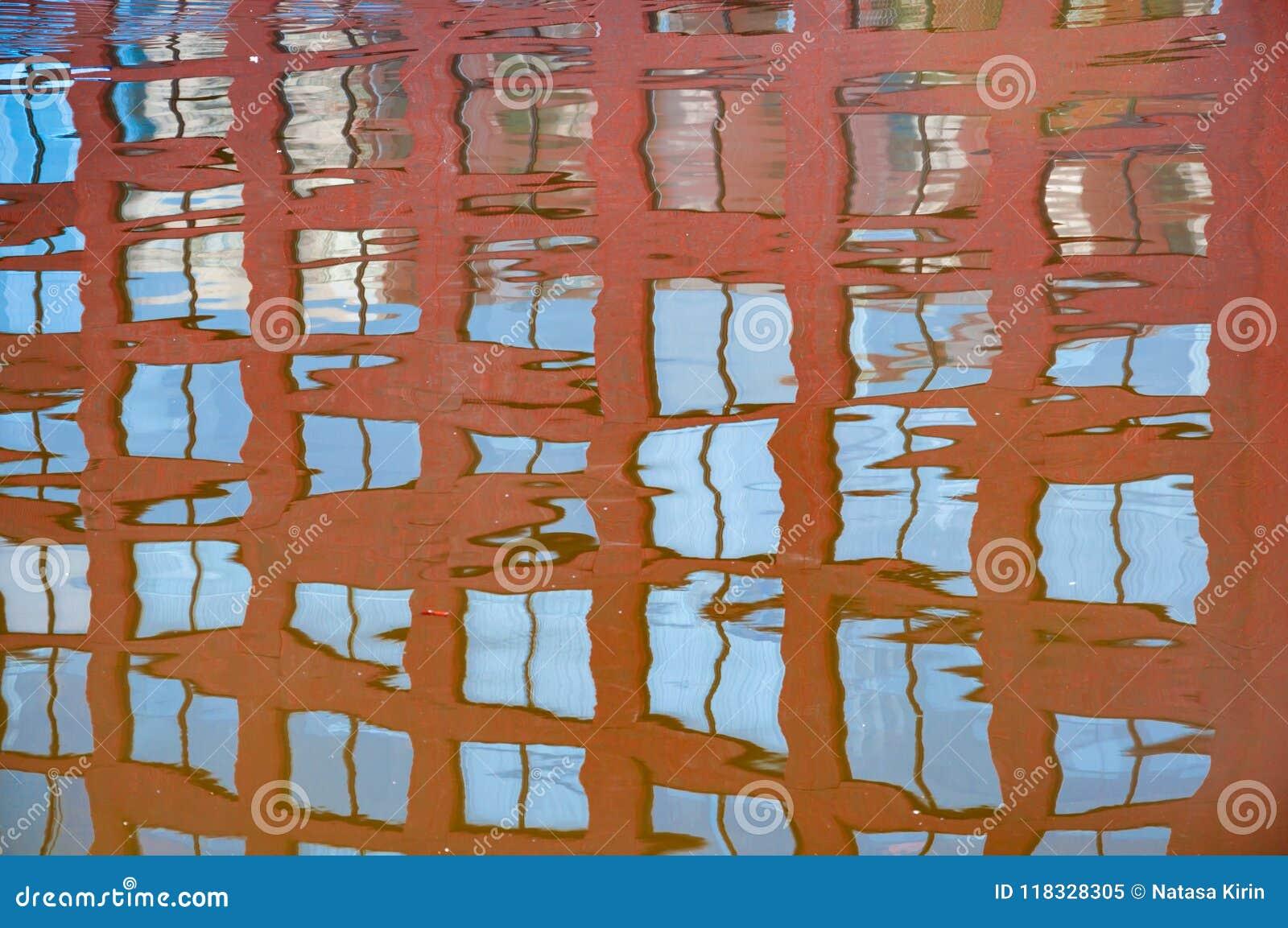 Reflexión de las ventanas del edificio en el río relativamente tranquilo