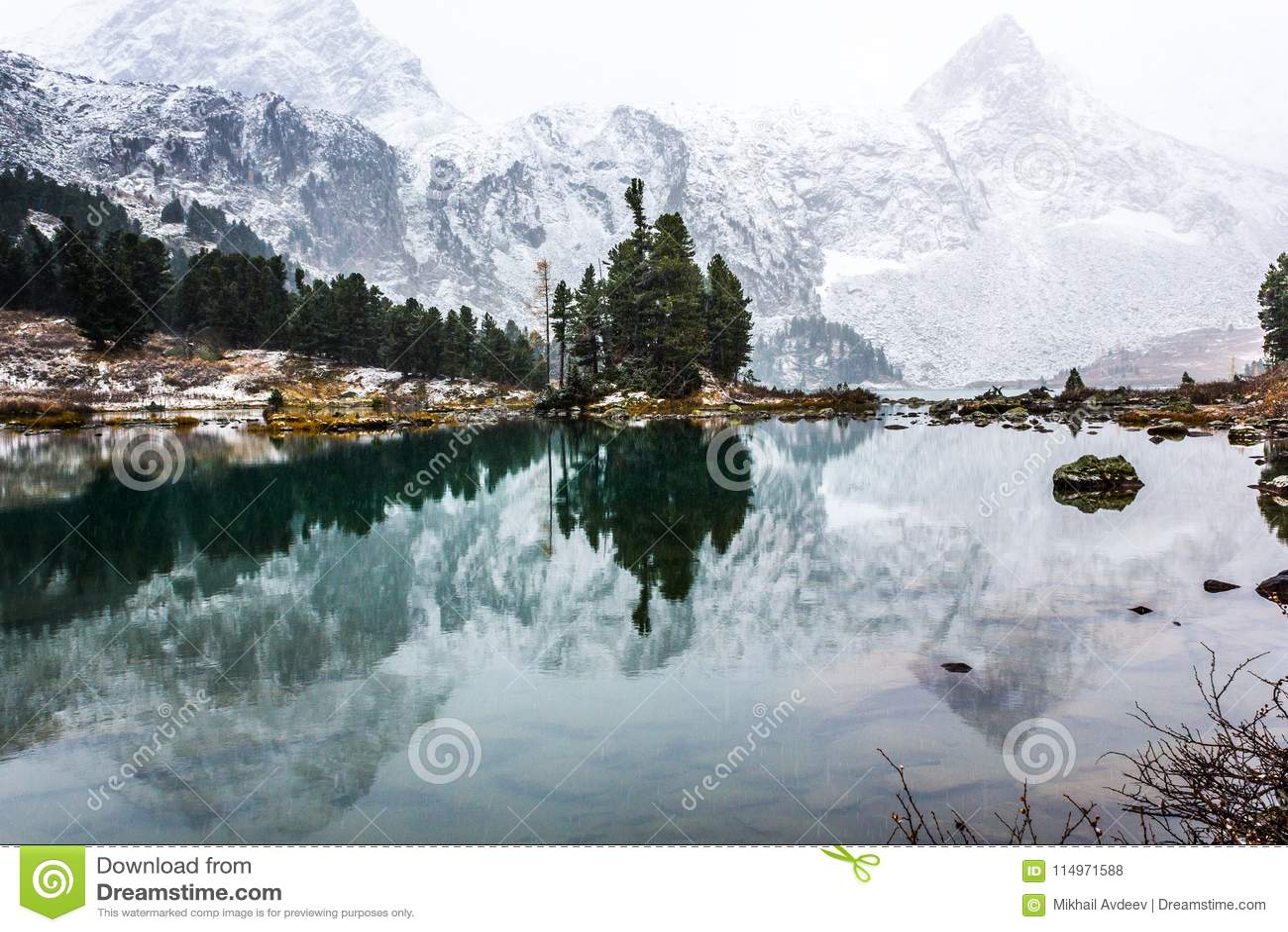 Reflexión de montañas con los picos nevosos