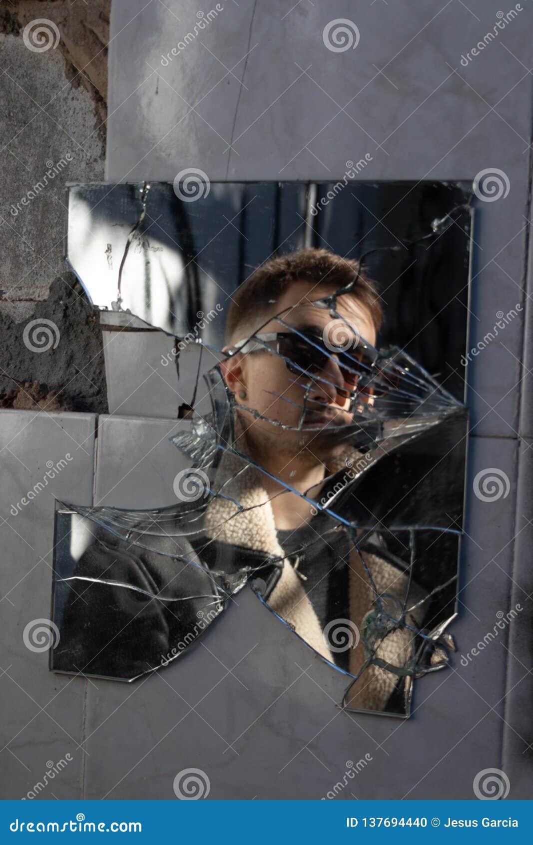 Reflexión del muchacho con las gafas de sol en un espejo quebrado