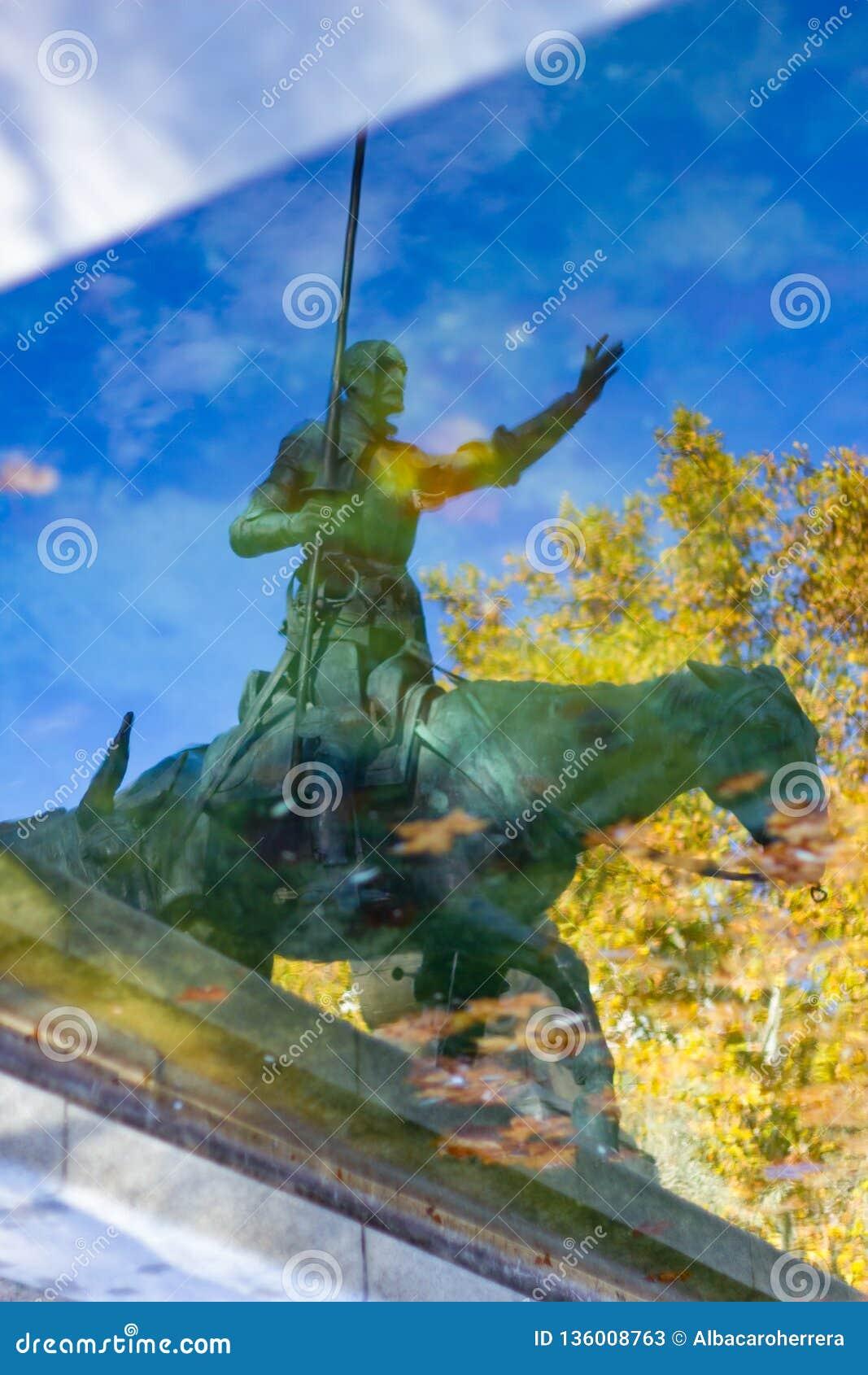 Reflexión en el agua de una estatua de Don Quixote